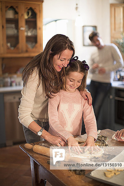 Mother and daughter cutting shapes in dough to make homemade cookies