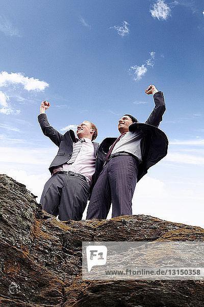 Businessmen cheering on cliff edge