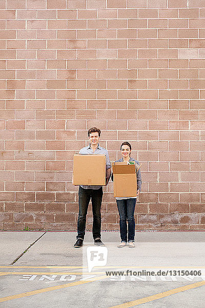 Portrait of young couple holding cardboard boxes in loading bay