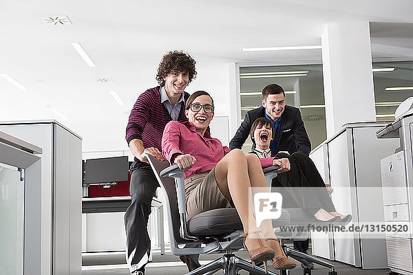 Office workers pushing women on office chairs