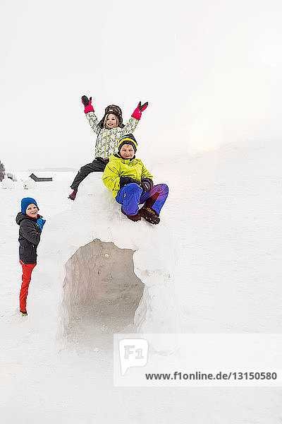 Two children sitting on top of igloo  boy standing beside it