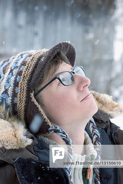 Young man looking in the snowy sky