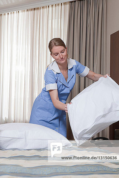 room maid fluffing up pillow room maid fluffing up pillow