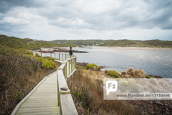 Photographer standing on wooden walkway  taking photographs of view  Tasmania