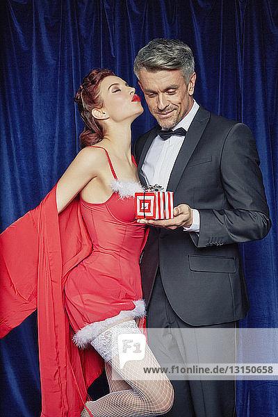 Burlesque woman giving husband Christmas gift Burlesque woman giving husband Christmas gift
