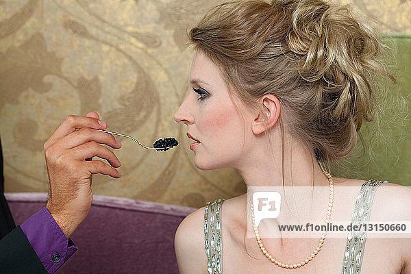 Man feeding girlfriend caviar