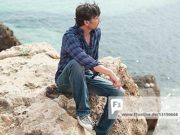 man sitting on rock at cliffs