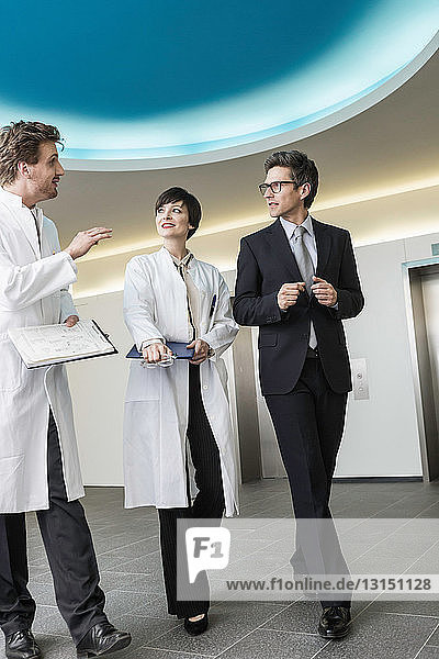 Three mid adults walking through lobby  wearing lab coats and business attire