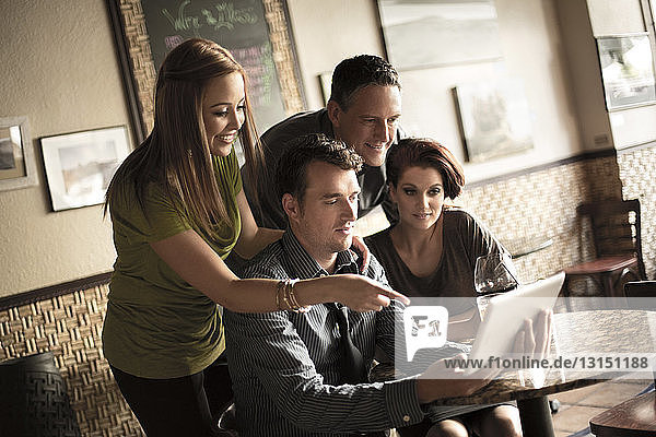 Friends looking at digital tablet in wine bar