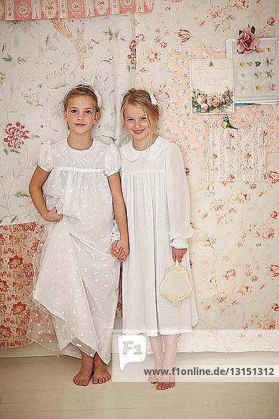 Girls holding hands in bedroom
