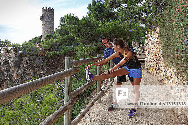 Couple stretching on castle wall