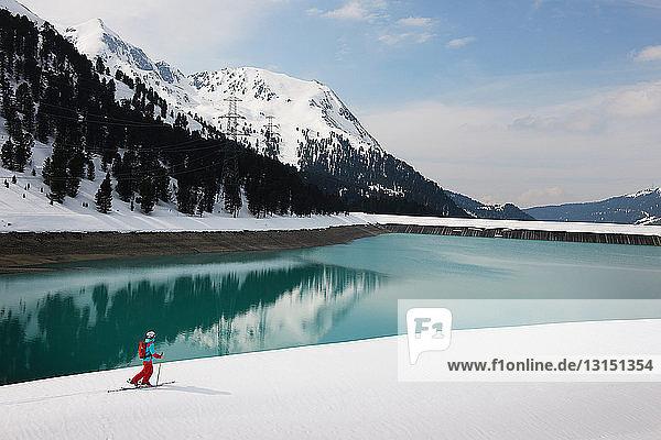 Solitary skier by lake and mountain  Kuhtai  Austria