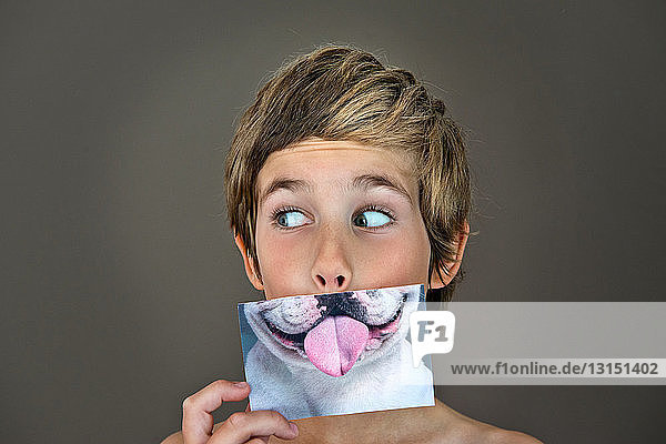 Boy holding picture of dog over face
