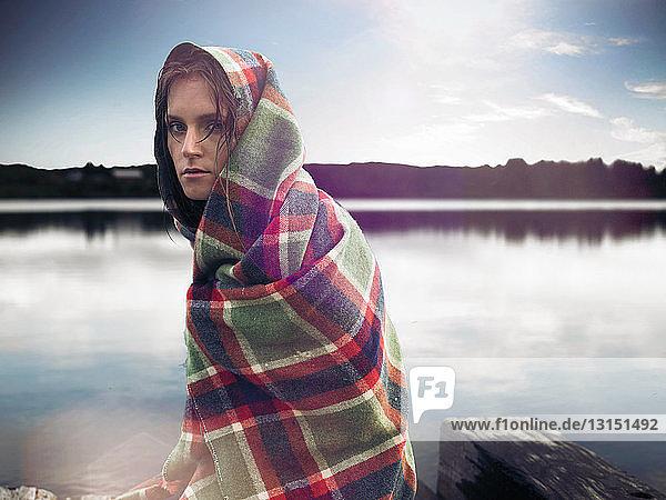 Woman in blanket on dock by lake