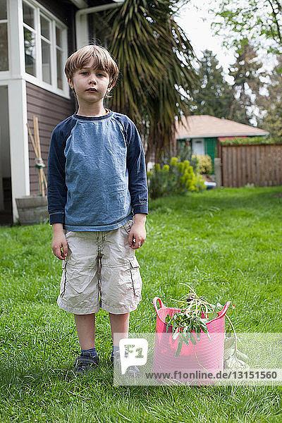 Boy standing in garden next to gardening refuse Boy standing in garden next to gardening refuse