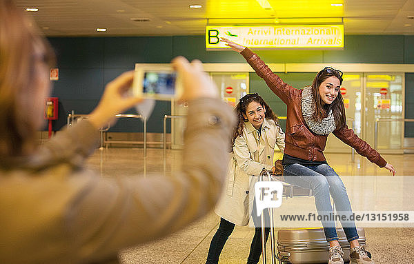 Woman photographing two teenage girls in airport