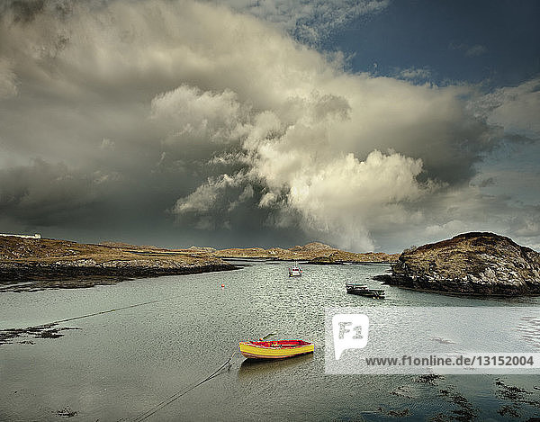Boats moored in natural sea harbor with storm clouds  Isle of Barra  Hebrides  Scotland  UK