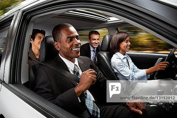 Businessmen and women haring car to work
