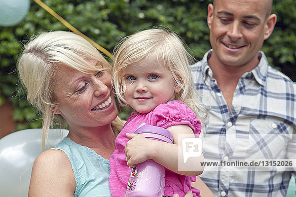 Happy mother and father with toddler daughter