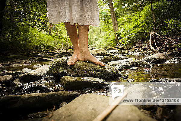 Bare feet of mid adult woman wearing white dress balancing on rock in riverbed
