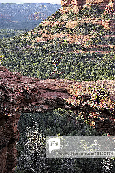 Female hiker jumping mid air on arched rock formation  Sedona  Arizona  USA