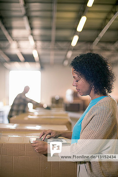 Female warehouse worker using digital tablet