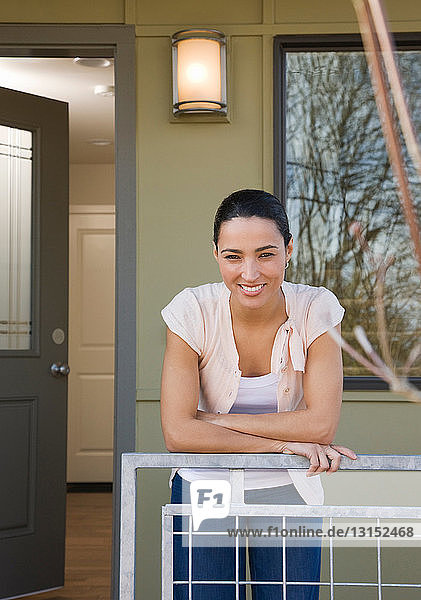 woman on front porch with sold sign