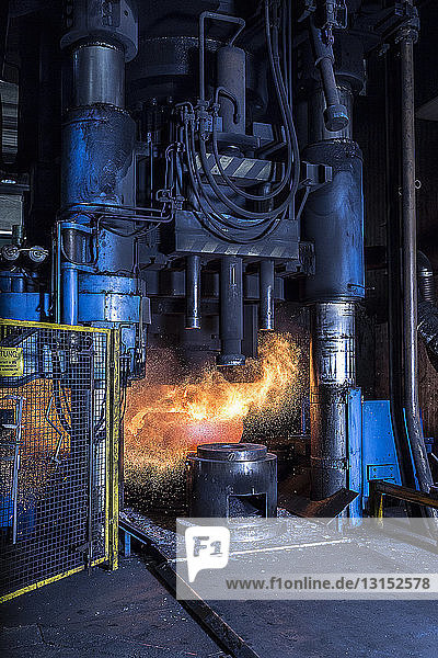 Manufacturing machine shaping red hot steel in foundry