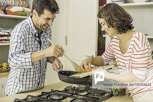 Couple preparing to cook fresh vegetables in kitchen