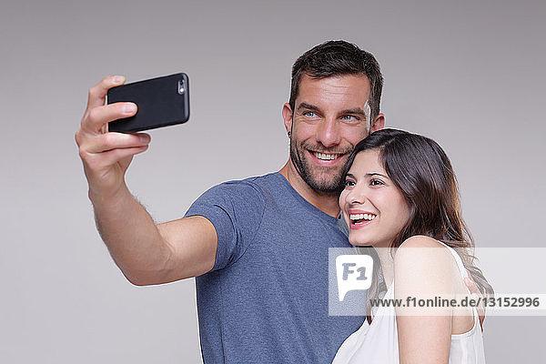 Heterosexual couple  taking self portrait  using smartphone