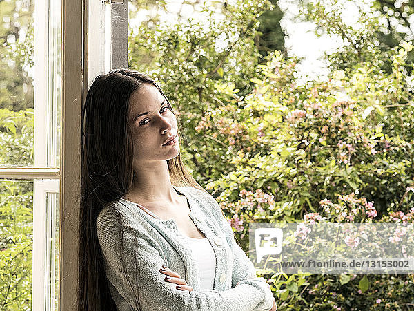 Portrait of young woman leaning against door frame