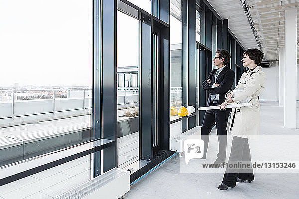 Architects looking out of window with blueprint