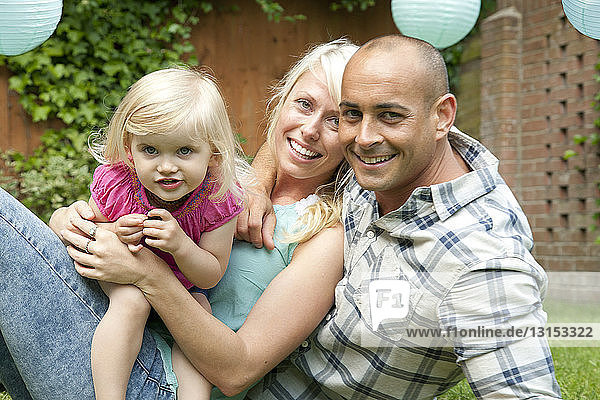 Portrait of happy couple sitting with toddler daughter in garden