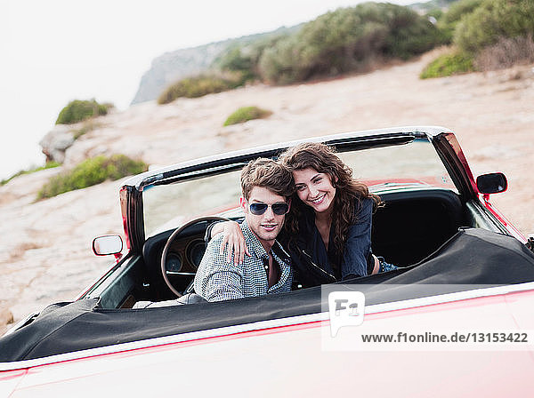 couple in car front seat embracing