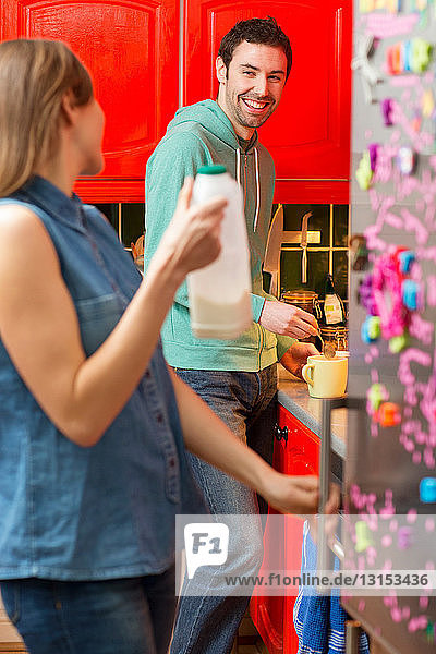 Young couple in kitchen  woman fetching milk from fridge