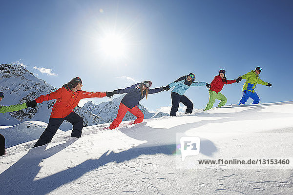 Friends pulling each other uphill in snow  Kuhtai  Austria