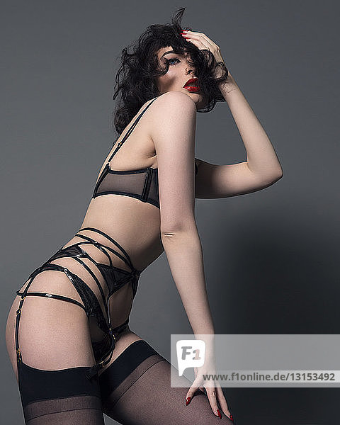 Portrait of young woman wearing suspenders  posing erotically