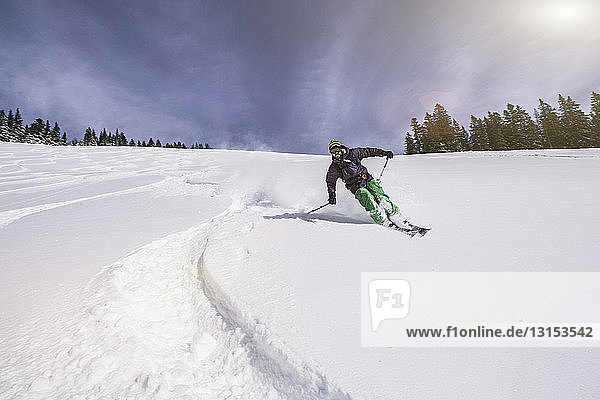 Male skier swerving down snow covered slope  Spitzingsee  Germany