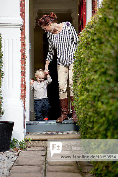 Mother helping toddler son over front doorstep