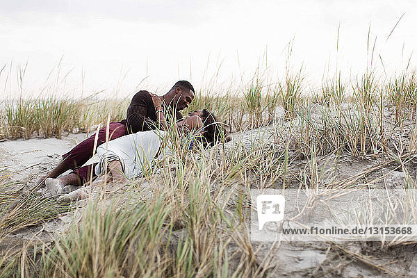 Couple lying in sand dunes  face to face