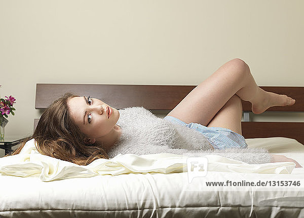 Portrait of sexy young woman lying on bed