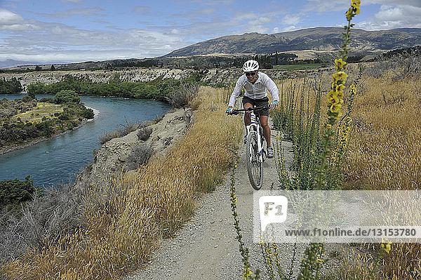 Female mountain biker on track,  New Zealand