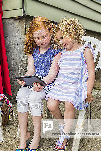 Two girls sitting on patio looking at digital tablet