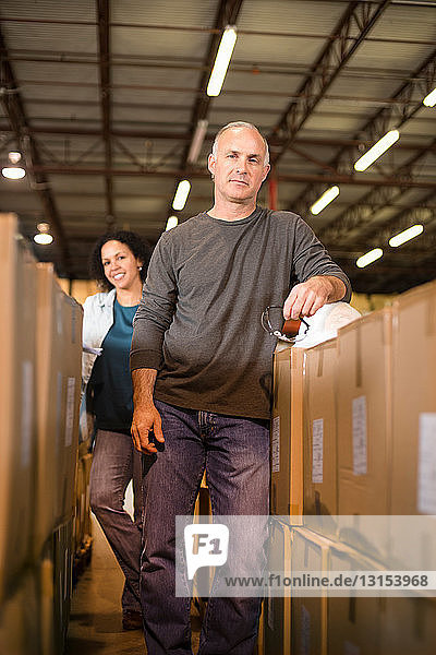 Portrait of warehouse workers by cardboard boxes