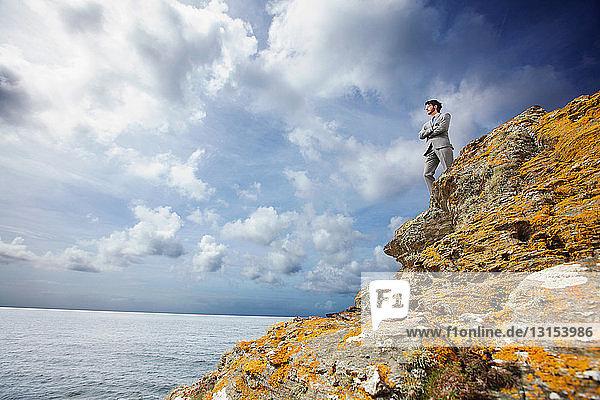 Businessman standing on cliff edge
