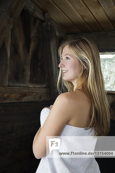 Young woman standing in sauna wrapped in white towel