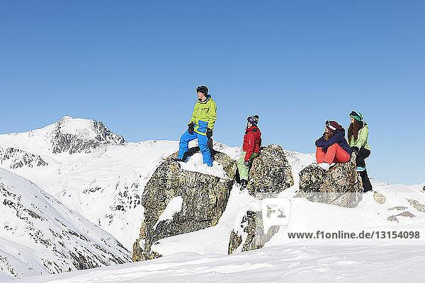 Friends on rocks in snow  Kuhtai  Austria