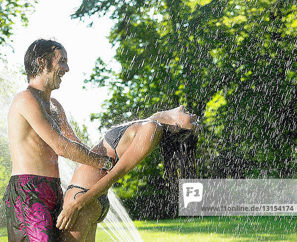 Couple dancing under a water-jet
