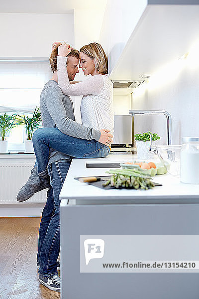 Couple hugging in kitchen  woman sitting on kitchen counter