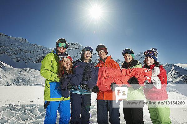 Friends holding woman in snow  Kuhtai  Austria